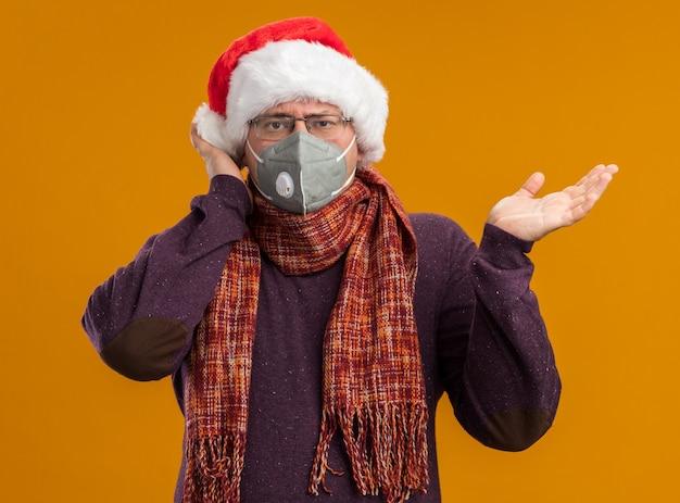 Uomo adulto impressionato che indossa occhiali maschera protettiva e cappello da babbo natale con sciarpa intorno al collo guardando la telecamera che mostra la mano vuota toccando la testa isolata su sfondo arancione Foto Gratuite