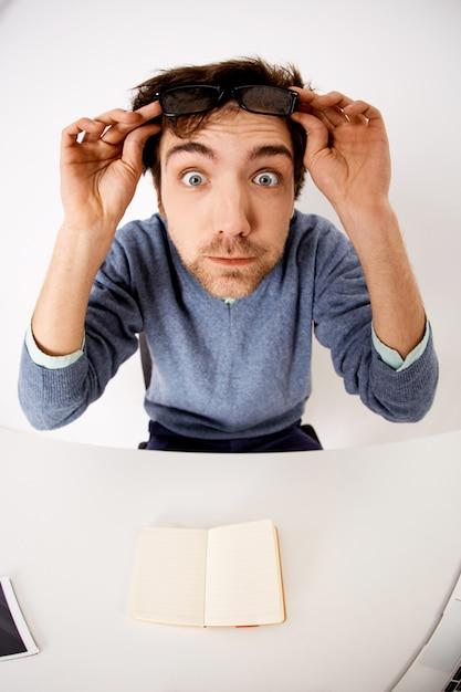 Впечатленный и удивленный молодой удивленный человек снимает очки, высунул глаза, сидя на офисном столе Бесплатные Фотографии