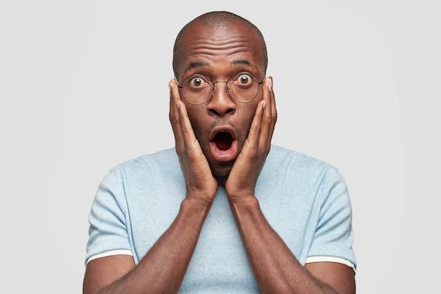 Il maschio afroamericano stupito impressionato mantiene la mascella aperta Foto Gratuite
