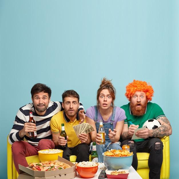 Impressionato quattro amici che trascorrono il tempo libero a casa, scioccati mentre guardano interessanti partite emozionanti, bevono birra fredda, fissano con gli occhi spalancati Foto Gratuite