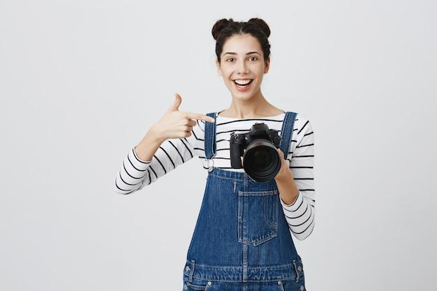 カメラのディスプレイで指を指している印象的な女の子の写真家、素晴らしいショットを称賛、素晴らしいモデルの仕事 無料写真
