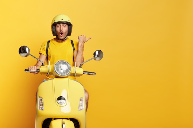 Impressed guy with helmet driving yellow scooter Free Photo