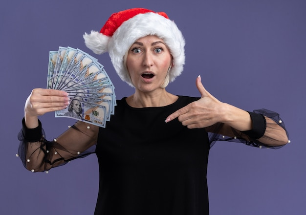 Impressed middle-aged blonde woman wearing christmas hat holding and pointing at money  isolated on purple wall Free Photo