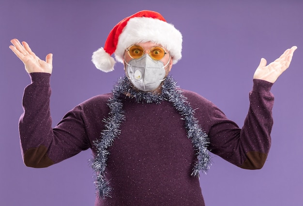 Impressionato uomo di mezza età che indossa un cappello da babbo natale e una ghirlanda di orpelli intorno al collo con occhiali e maschera protettiva che guarda l'obbiettivo Foto Gratuite