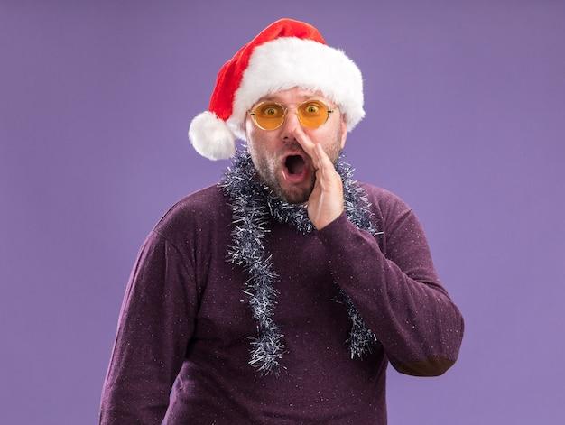 Uomo di mezza età impressionato che indossa un cappello da babbo natale e una ghirlanda di orpelli intorno al collo con gli occhiali che bisbigliano isolato sul muro viola Foto Gratuite