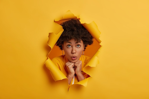 Impressed surprised young woman, keeps hands pressed together under chin, poses in torn yellow paper hole background Free Photo