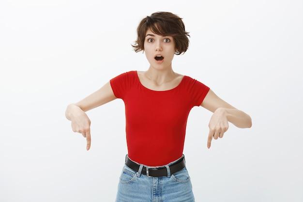 감동적인 여자가 와우라고 말하고 발표에서 손가락을 아래로 가리키고 있습니다. 무료 사진