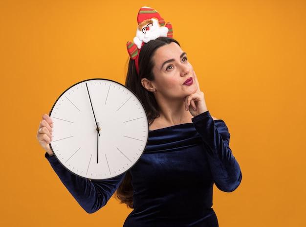Impressionato giovane bella ragazza che indossa abito blu e cerchio di capelli di natale che tiene l'orologio di parete che mette la mano sulla guancia isolata sulla parete arancione Foto Gratuite
