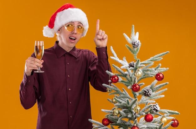 Impressionato giovane uomo biondo che indossa il cappello della santa e bicchieri in piedi vicino all'albero di natale decorato tenendo un bicchiere di champagne guardando il lato rivolto verso l'alto isolato su sfondo arancione Foto Gratuite