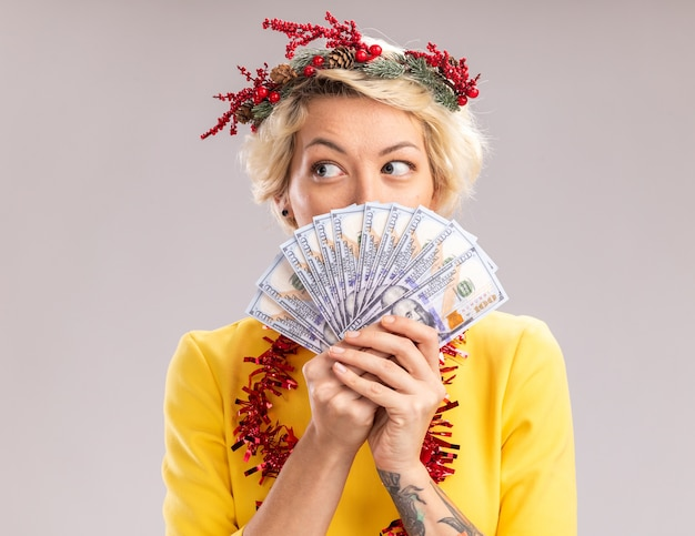 Impressed young blonde woman wearing christmas head wreath and tinsel garland around neck holding money looking at side from behind it isolated on white wall Free Photo