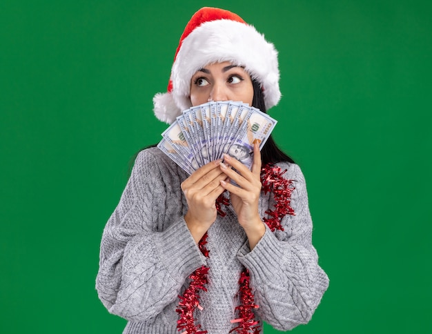Impressed young caucasian girl wearing christmas hat and tinsel garland around neck holding money looking at side from behind it isolated on green wall with copy space Free Photo