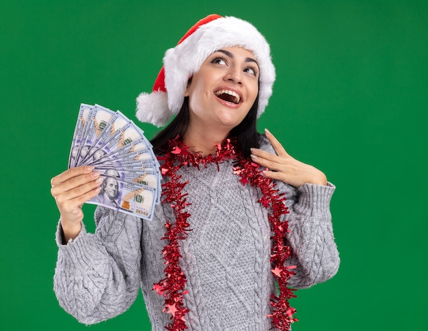 Impressed young caucasian girl wearing christmas hat and tinsel garland around neck holding money touching shoulder looking up isolated on green wall Free Photo