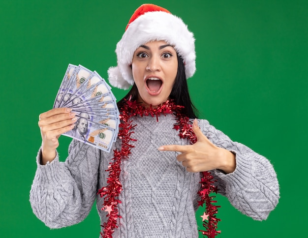 Impressed young caucasian girl wearing christmas hat and tinsel garland around neck holding and pointing at money  isolated on green wall Free Photo
