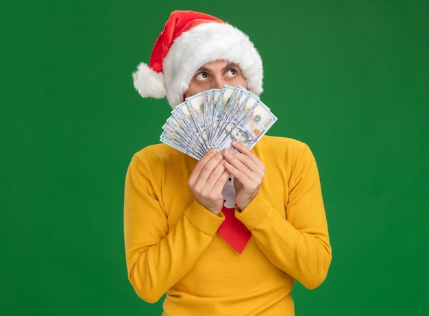 Impressed young caucasian man wearing christmas hat and tie holding money looking up from behind it isolated on green wall with copy space Free Photo