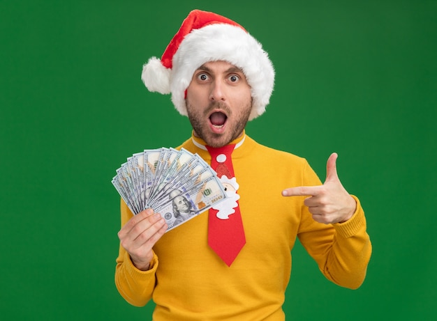 Impressed young caucasian man wearing christmas hat and tie holding and pointing at money isolated on green wall Free Photo