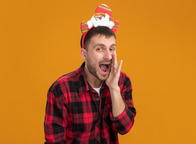 Impressionato giovane uomo caucasico che indossa la fascia di babbo natale tenendo la mano vicino alla bocca sussurrando isolato sulla parete arancione con lo spazio della copia Foto Gratuite