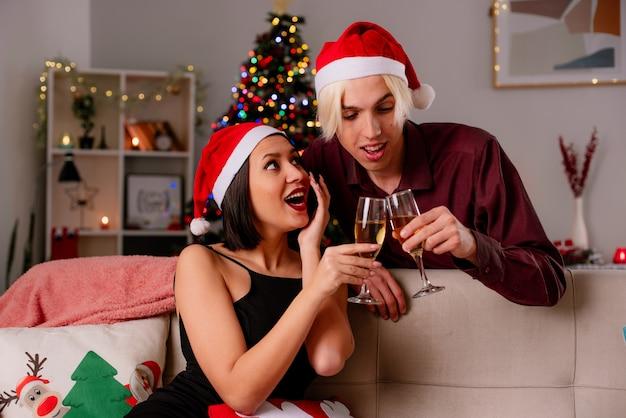 Impressionato giovane coppia a casa nel periodo natalizio indossando il cappello della santa tenendo un bicchiere di champagne Foto Gratuite
