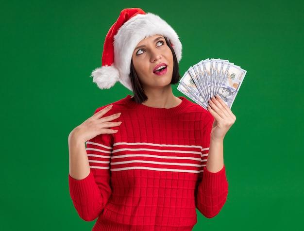 녹색 벽에 고립 된 찾고 어깨를 만지고 돈을 들고 산타 모자를 쓰고 감동 어린 소녀 무료 사진