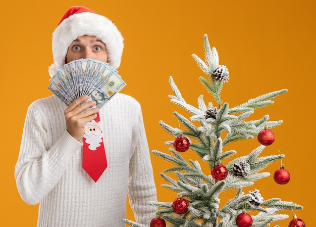 Impressed young handsome guy wearing christmas hat and santa claus tie standing near decorated christmas tree holding money  from behind it isolated on orange wall Free Photo