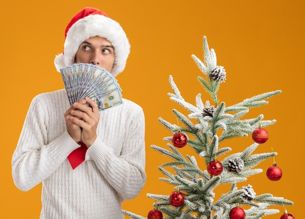 Impressed young handsome guy wearing christmas hat and santa claus tie standing near decorated christmas tree holding money looking at side from behind it isolated on orange wall Free Photo