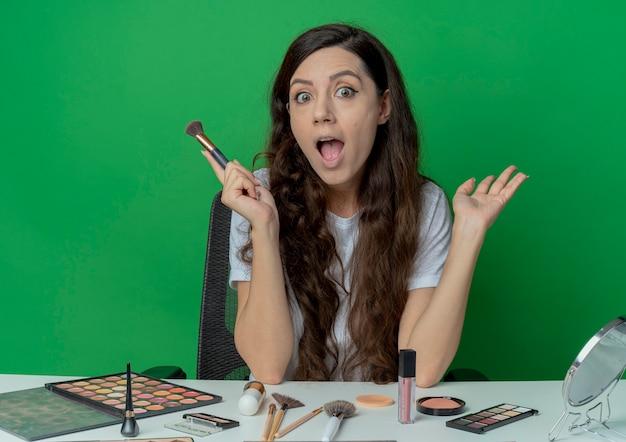 赤面ブラシを保持し、緑の背景に分離された空の手を示す化粧ツールで化粧テーブルに座っている感動の若いかわいい女の子 無料写真