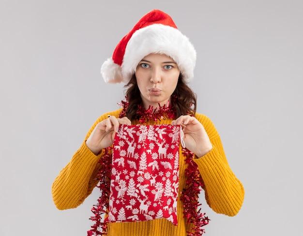 サンタの帽子とコピースペースで白い背景に分離されたクリスマスギフトバッグを保持している首の周りに花輪を持つ印象的な若いスラブの女の子 無料写真