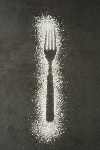 Imprint fork silhouette made of flour on a black background Premium Photo