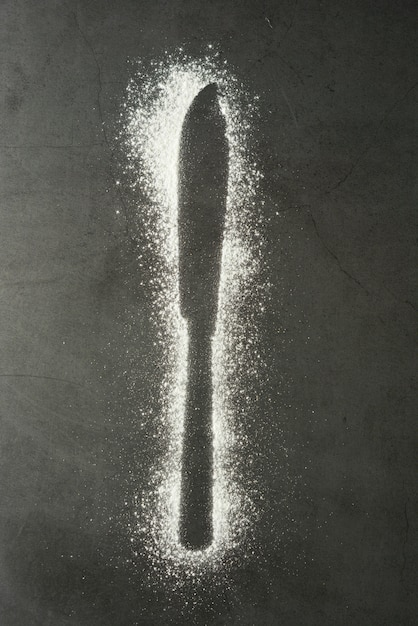 Imprint knife silhouette made of flour on a black background Premium Photo