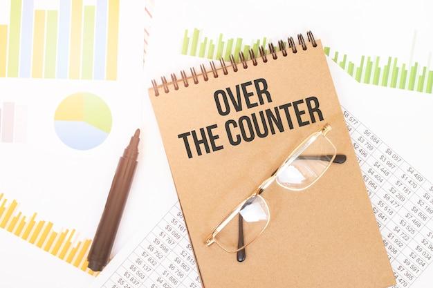 공예 컬러 노트에는 연필, 안경, 그래프 및 다이어그램 옆에 Over The Counter 비문이 있습니다. 프리미엄 사진