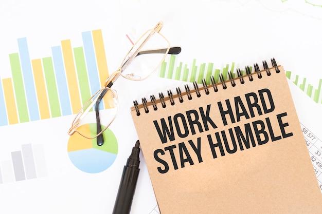 공예 컬러 노트에는 연필, 안경, 그래프 및 다이어그램 옆에 Work Hard Stay Humble 비문이 있습니다. 프리미엄 사진