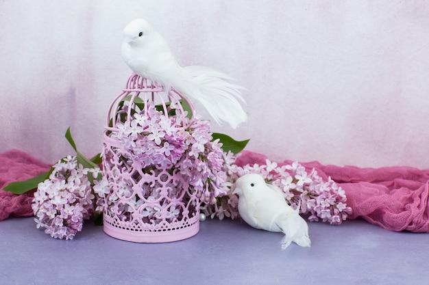 В розовой клетке розовая сирень и два белых голубя Premium Фотографии