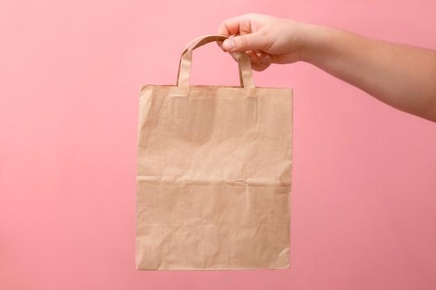 ピンクの背景に女性の紙袋の手に Premium写真