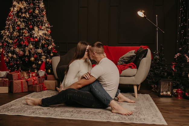 Влюбленная пара мужчина и женщина, сидящие на полу, скрестив ноги, обнимаются и целуют елку Premium Фотографии