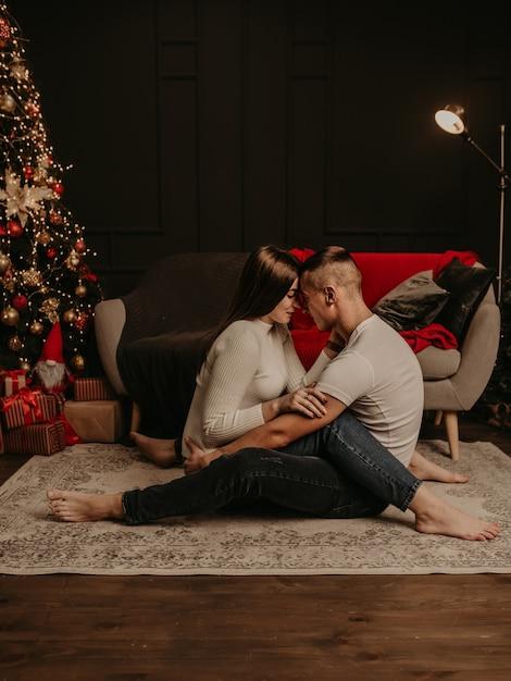 사랑 커플 남자와여자가 바닥에 앉아 포옹 포옹과 키스 크리스마스 트리 프리미엄 사진