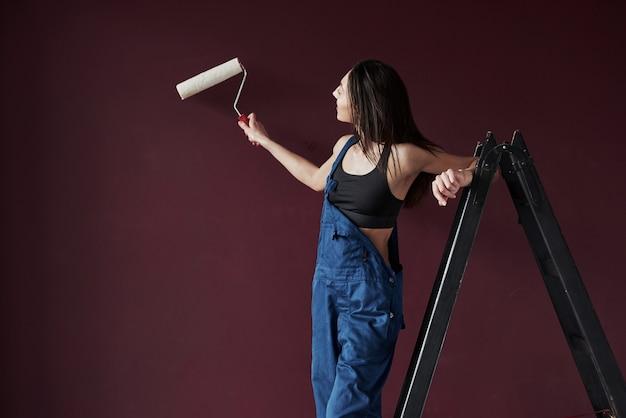 塗装中です。部屋の新しい家に壁紙を接着することにした若い主婦 無料写真
