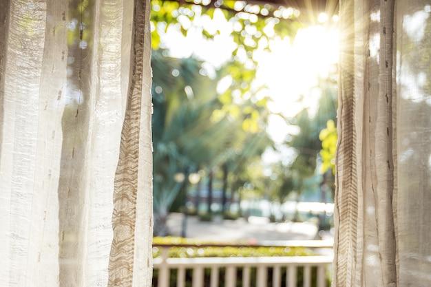 朝、白いカーテンを通して太陽がドアを照らします。 Premium写真