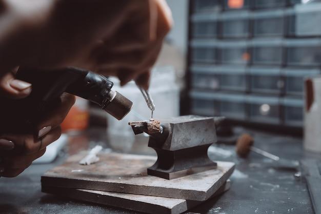 В мастерской женщина-ювелир занята пайкой ювелирных изделий Бесплатные Фотографии
