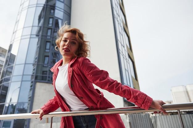 白いシャツ。暖かい赤いコートを着た大人のきれいな女性が彼女の週末の時間に街を歩いている 無料写真