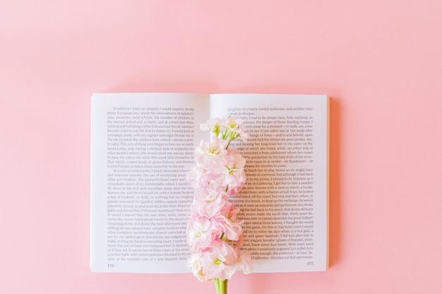 Вид сверху раскрытой книги и розовая маттиола incana или матильда лаванда на пастельно-розовый фон с копией пространства Premium Фотографии