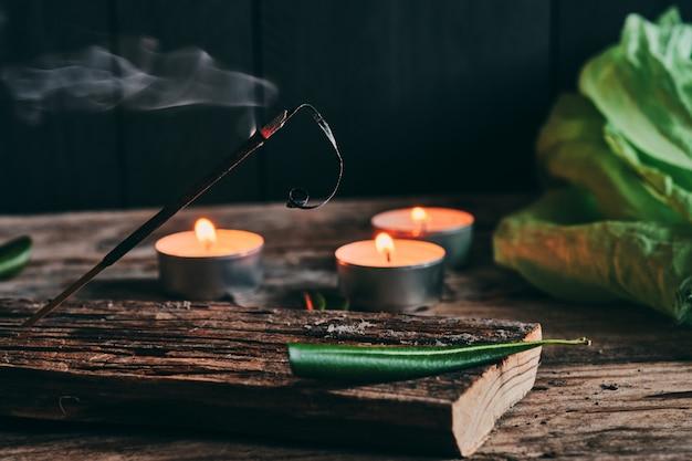 Ароматические палочки и свечи на деревенском дереве Premium Фотографии