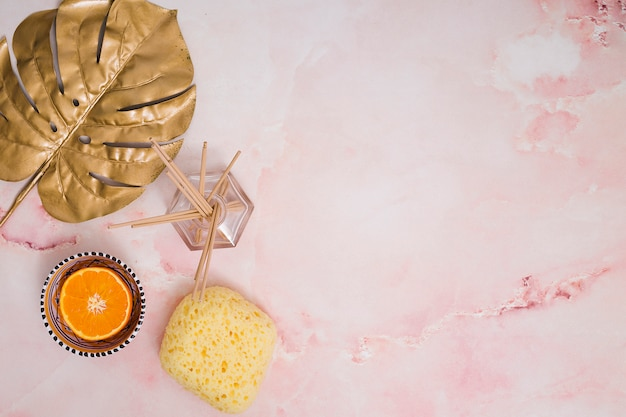 Incense sticks in glass bottle; halved orange fruit; monstera leaf and yellow pumice stone on pink textured background Free Photo