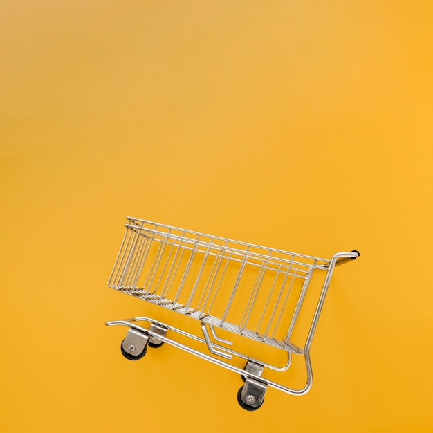 Inclined shopping cart in yellow background Free Photo
