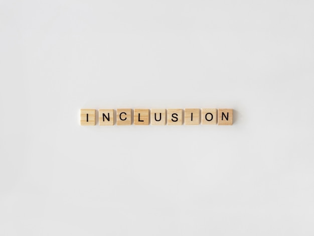 Inclusion word written in scrabble letters on white background Free Photo