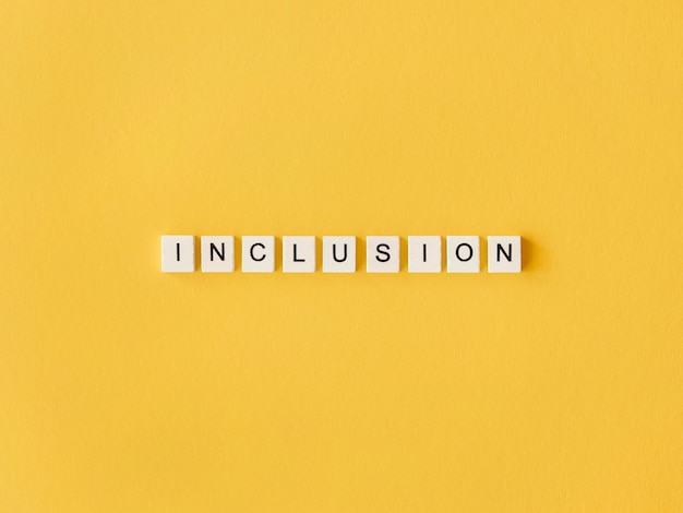 Inclusion word written in scrabble letters on yellow background Free Photo