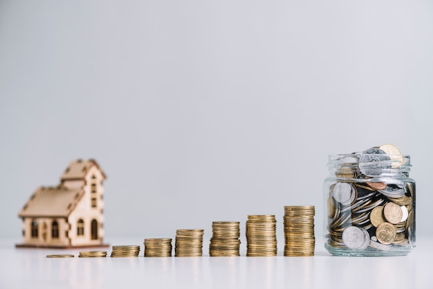 Increasing stacked coins and glass jar in front of house model Free Photo