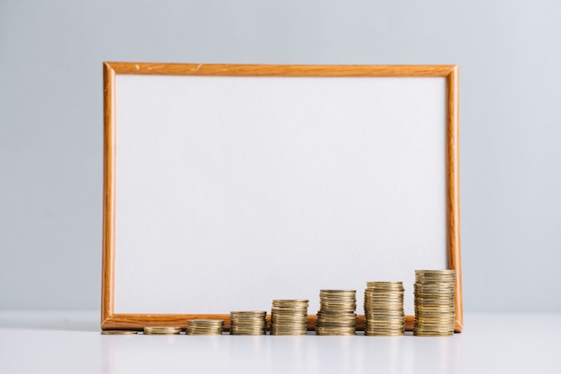 Increasing stacked coins in front of blank white board Free Photo
