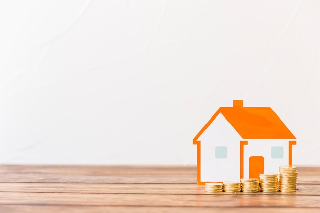 Increasing stacked coins and house model in front of wall Free Photo