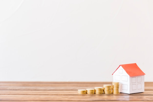 Increasing stacked coins near house model on wooden desk Free Photo