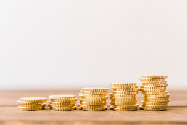 Increasing stacked coins on wooden desk Free Photo
