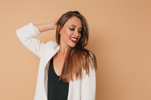 Невероятная стильная улыбающаяся женщина с помадой из винограда в белом пиджаке позирует над бежевой стеной, готовится к вечеринке, изолированная стена Бесплатные Фотографии
